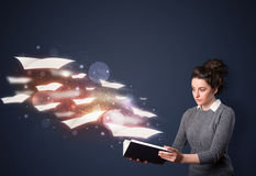 Young lady reading a book with flying sheets coming out of the b Stock Images