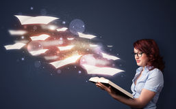 Young lady reading a book with flying sheets coming out of the b Stock Photos