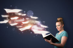 Young lady reading a book with flying sheets coming out of the b Stock Photography