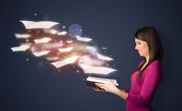 Young lady reading a book with flying sheets coming out of the b Stock Photo