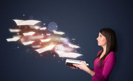 Young lady reading a book with flying sheets coming out of the b Stock Image