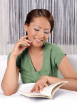 Young lady reading a book while lying on bed Royalty Free Stock Images
