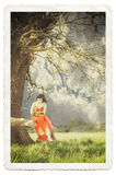 Young lady reading a book under a tree. Female reading book under tree, vintage photograph look. Textured, gritty detail with soft focus, cracks and borders Royalty Free Stock Photography
