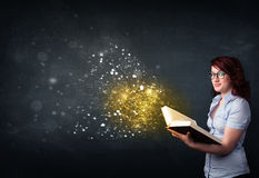 Young lady reading a magical book Stock Image