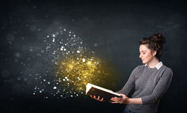 Young lady reading a magical book Stock Images