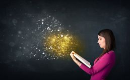 Young lady reading a magical book Royalty Free Stock Photography