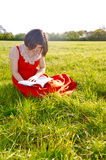 A young lady reading in nature. A young woman sitting on the grass and reading a book, on a sunny day Royalty Free Stock Photo