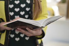 Young lady reads a book. Woman`s hands holding the book Stock Photo