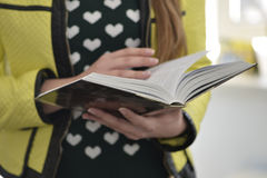 Young lady reads a book. Woman`s hands holding the book Royalty Free Stock Photos
