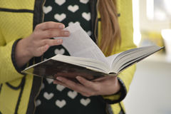 Young lady reads a book. Woman`s hands holding the book Stock Images