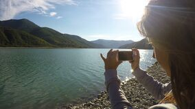 Young lady recording video of sunlit mountain scenery and river using smartphone. Stock footage stock video footage