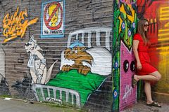 Young lady in red and cartoon characters. LONDON, GREAT BRITAIN, April 22, 2018 : Young lady in red poses in front of an artistic graffiti of cartoon characters royalty free stock image