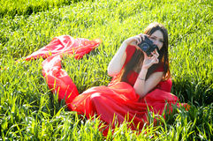 Young lady in red dress with camera on field royalty free stock image