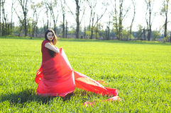 Young lady in red dress on field Stock Image