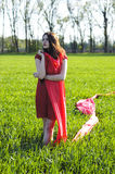 Young lady in red dress on field Stock Photos