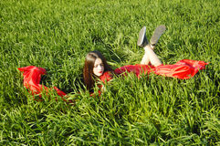 Young lady in red dress lie on field Royalty Free Stock Photography