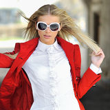 Young lady in red dress posing outdoors wearing sunglasses Royalty Free Stock Photography