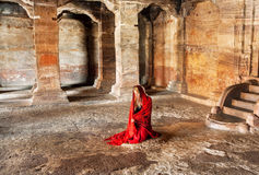 Young lady in red dress praying on the floor of ancient cave temple in Karnataka, India Royalty Free Stock Photos