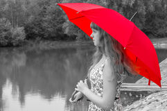 Young lady with red umbrella near the pond Stock Image