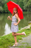Young lady with red umbrella near the pond Royalty Free Stock Images