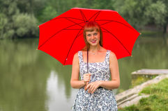 Young lady with red umbrella near the pond Royalty Free Stock Image