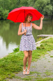 Young lady with red umbrella near the pond Stock Photos