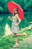 Young lady with red umbrella near the pond Stock Photo