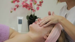 The young lady is relaxing on the couch during the spreading the creme on her skin in salon. cosmetologist.  stock video