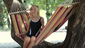 Young lady relaxing on hammock on a beach stock video footage