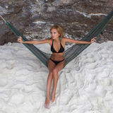 Young lady relaxing in hammock on the sandy beach royalty free stock photography