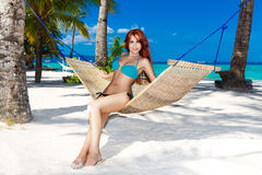 Young lady relaxing in hammock on the tropical beach.  Stock Photo