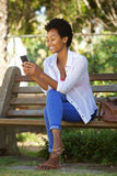 Young lady relaxing a park bench and using mobile phone Stock Images