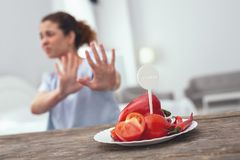 Young lady restricting herself in vegetables. No red vegetables. Young lady holding her hands against a plate of red vegetables while being terrible allergic to Stock Image