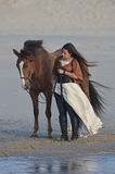 Young lady riding a horse at beach in early morning Royalty Free Stock Images