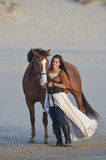 Young lady riding a horse at beach in early morning Stock Photo