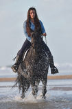 Young lady riding a horse at beach in early morning Royalty Free Stock Photography