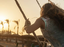 Young lady riding on a swing at sunset on a background of palm t Stock Photo