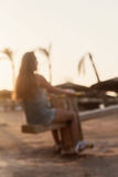 young lady riding on a swing at sunset on a background of palm t Royalty Free Stock Photos