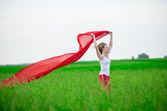Young lady runing with tissue in green field Royalty Free Stock Image
