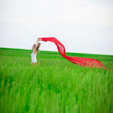 Young lady runing with tissue in green field Stock Photography