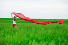 Young lady runing with tissue in green field. Woman with scarf. Stock Image
