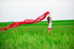Young lady runing with tissue in green field. Woman with scarf. Royalty Free Stock Photos