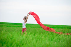 Young lady runing with tissue in green field. Woman with scarf. Stock Images