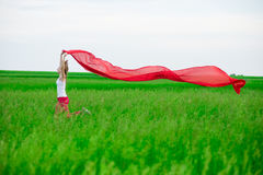 Young lady runing with tissue in green field. Woman with scarf. Royalty Free Stock Image