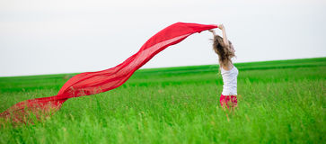 Young lady runing with tissue in green field. Woman with scarf. Stock Photos