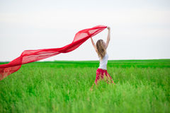 Young lady runing with tissue in green field. Woman with scarf. Royalty Free Stock Photo