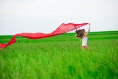 Young lady runing with tissue in green field. Woman with scarf. Stock Photo