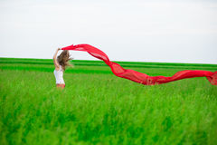 Young lady runing with tissue in green field. Woman with scarf. Royalty Free Stock Photography