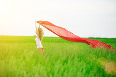 Young lady runing with tissue in green field. Woman  scarf. Stock Photos