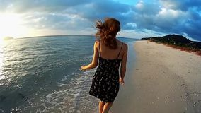 Young lady running on the beach at sunset stock video footage